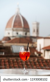 "Florence, Tuscany/ Italy. October 1, 2018. A glass of Italian cocktail ""aperol spritz"" on the background of the Cathedral of Santa Maria del Fiore in the center of Florence. two symbols of Italy"