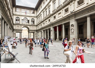 FLORENCE,ITALY-AUGUST 26,2014:Many tourists strolling in the Uffizi gallery in the middle of the street artist or to go to the museums during a cloudy day.