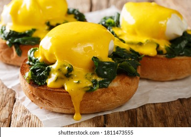 Florentine eggs with spinach and hollandaise sauce on a crispy bun close-up on the table. horizontal