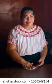 Flores / Guatemala - May 3, 2016: Mayan woman making tortillas while posing for camera in Flores, Guatemala, Central America.