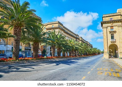 FLORIANA, MALTA - JUNE 17, 2018: The lush green palms and scenic flower beds on St Anna street with many stores in old edifices, on June 17 in Floriana.