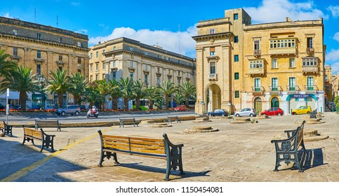 FLORIANA, MALTA - JUNE 17, 2018: Panorama of Robert Samut square with capstones of granaries in the middle, surrounded by row of benches and St Anne avenue on background, on June 17 in Floriana.