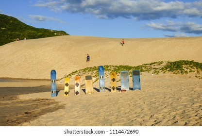 Florianopolis, Brazil - Circa May 2018: Colorful sandboards at Ingleses beach, kids playing on the sand dunes in the background