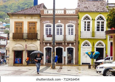 Florianopolis, Brazil - Circa October 2016: Man walking with an umbrella on a rainy day in Florianopolis city center - old colonial buildings in the background