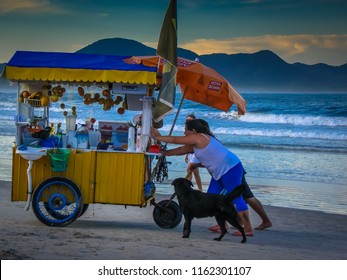 Florianopolis/SC/Brazil - 01-30-2010: People pushing the cart of fruits and juices on the beach of Barra da Lagoa in Florianopolis, Santa Catarina