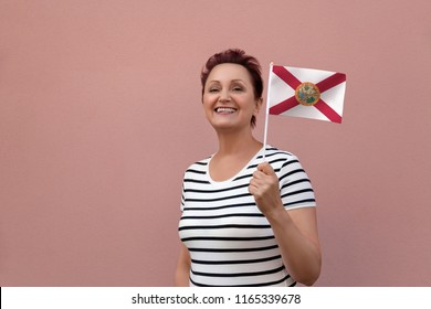 Florida flag. Woman holding Florida state flag. Nice portrait of middle aged lady 40 50 years old with a national flag over pink wall background outdoors.