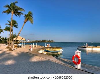 Florida Keys bayside sandy beach and dock on clear, blue sky morning