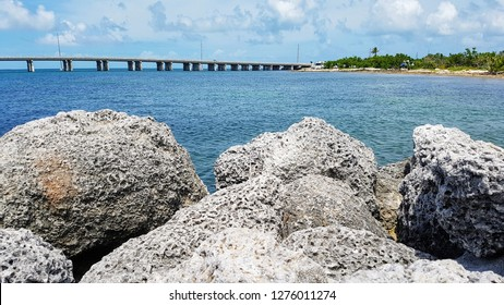 Florida Overseas highway concrete bridge over blue ocean water of Gulf of Mexico, Calusa beach in Florida Keys landscape, Bahia Honda State Park, azure green shallow water, coral reef stones on beach