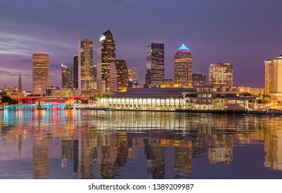 Florida skyline at Tampa with the Convention Center on the riverbank. Lights are reflected in a smooth artificial water  surface