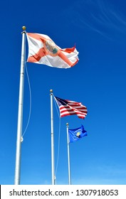 The Florida State Flag, the American Flag, and the Key West Conch Republic Flag waving from three flag poles, against blue sky.