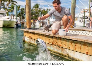 Florida tourism summer vacation attraction tourist man having fun feeding tarpon fish in the keys, USA travel lifestyle.