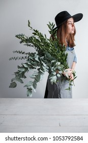 florist in apron makes a bouquet of eucalyptus leaves