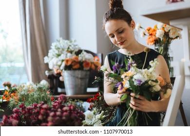 florist arranging a bouquet of beautiful colorful flowers inside her floral shop