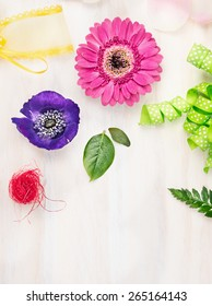 Florist background with flowers and accessories on white wooden background, top view, place for text