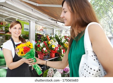 Florist business woman shop assistant holding and selling a bouquet of fresh flowers to an attractive woman customer during a sunny day in a kiosk store. Outdoors working business.