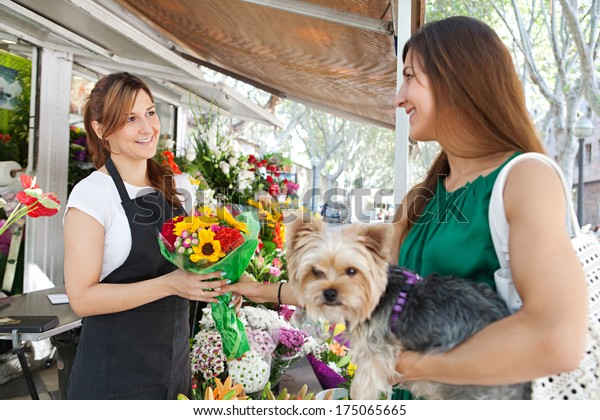 Florist business woman shop assistant selling a bouquet of fresh flowers to an attractive woman customer with her dog pet during a sunny day. Outdoors working business.