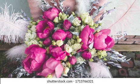 Florist girl holding beautiful flower arrangement. Pink and purple peonies with feathers in box. Romantic pink floral concept.