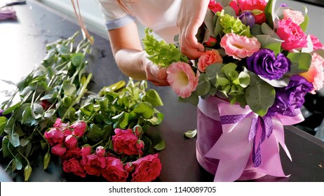 Florist girl makes a floral box in a flower salon, close-up. Woman preparing beautiful bouquet.