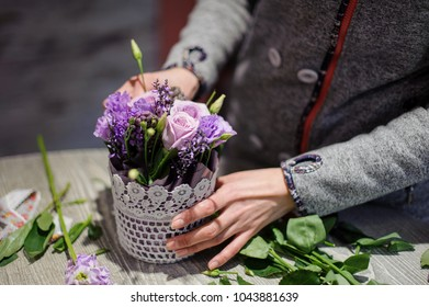 Florist hands making a pretty lilac bouquet of roses and other flowers in a pot