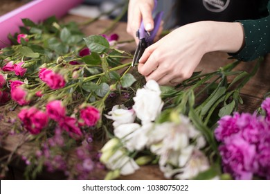 Florist leading small business, cutting flowers at the table in shop