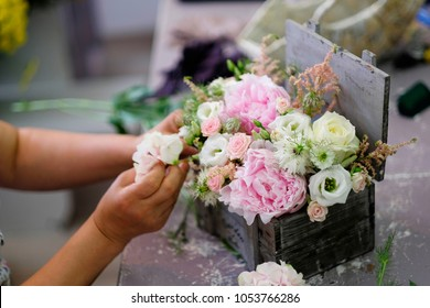 Florist made a floral arrangement. Florist woman prepare a floral arrangement for wedding event.