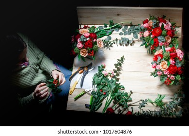the florist makes flower arrangement on a wooden table around the darkness