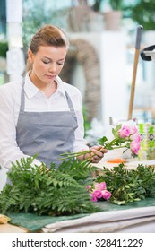 Florist making bouquet of fresh roses at counter in flower shop
