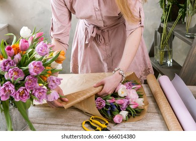Florist pack festive bouquet in wrapping paper. Young beautiful florist girl make floristry assemble with pink peony and wildflowers in workshop on wooden background. Woman's hand at work