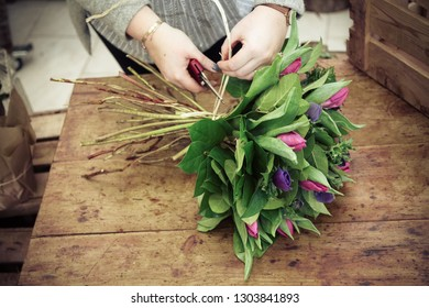 A florist preparing a bouquet on a vintage wood table