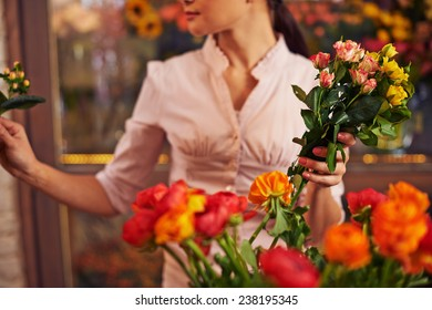 Florist with rose bunch working in shop