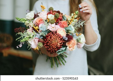 Florist shop in daylight. Woman holding beautiful bouquet of flowers. Florist with her work. Stylized tender photo with hipster filter.