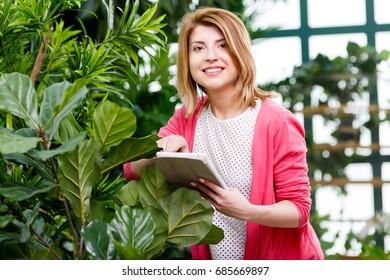 Florist with tablet near ficus