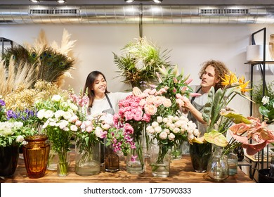 Florist team with many colorful flowers in the flower shop as a business