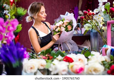 Florist woman creates flower bouquet of mixed flowers for delivery to client