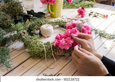 Florist at work: Creating a wooden wreath with branches pine and pink flowers, surrounded by the arts and crafts.