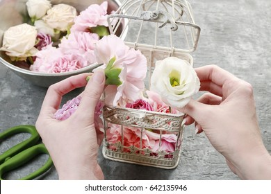 Florist at work: how to make wedding decoration with vintage birdcage and fresh flowers.
