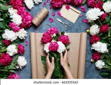 Florist at work: pretty woman making summer bouquet of peonies on a working gray table. Kraft paper, scissors, envelope for congratulations on the table. View from above. Flat lay composition.