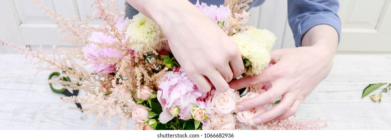 Florist at work: woman arranging bouquet with pink peonies, roses and yellow dahlias. Summer wedding flowers.