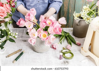 Florist at work: woman arranging flowers. Bouquet of pink tulips.