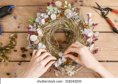 Florist at work: woman making door wreath with autumn plants and flowers