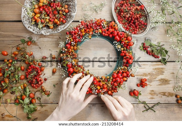 Florist at work: woman making rose hip and hawthorn wreath