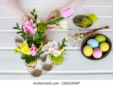 Florist at work: woman shows how to make Easter floral decoration with colorful eggs, tulips, freesias and buxus. Step by step, tutorial.