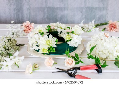 Florist at work: woman shows how to make wedding table decoration with wreath and candle inside the glass container. Step by step, tutorial.