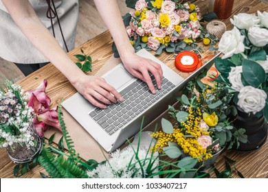 Florist working with laptop in a flower shop