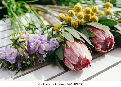 Florist working table with craspedia, freesia and protea flowers. Flowers delivery, creating order
