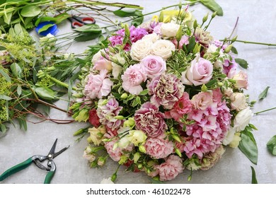 Florist workplace: how to make floral arrangement with pink carnation, rose and eustoma flower.