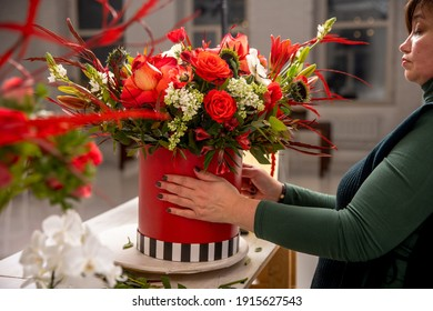 Florist workplace on the background of a white brick wall. A florist examines a floral arrangement of orchids, roses, sunflowers, lilies, alstroemerias and ornithogalums in a red box. Tutorial.