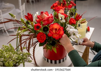 Florist workplace on the background of a white brick wall. The florist composes a bouquet of orchids, roses, sunflowers, lilies, alstemeria and ornithogalum, adding flowers to it step by step. Manual.