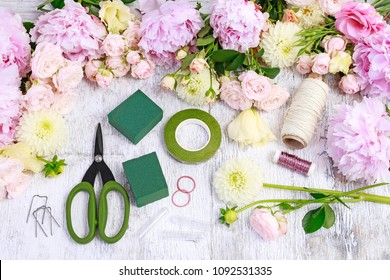 Florist workplace: Rose, lisianthus, dahlia, peony and florist's accessories on wooden table.