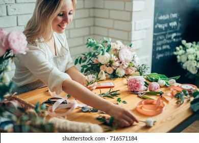 Florist workplace: woman arranging a bouquet with roses, matthiolas, ranunculus flowers and gypsophila paniculata twigs.